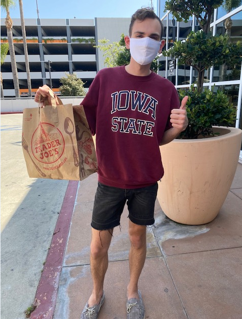 person holding bag of donated masks wearing a mask